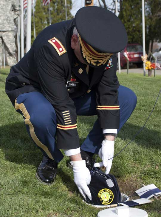 LTC Scheetz lowering the remains of a veteran into the Veterans Cremation Garden among the flats